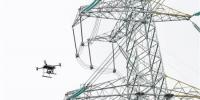 11月22日,重庆电网500千伏玉屏变电站外的高压电线塔旁,智能巡检无人机正在巡检高压线路(小图),智能巡检机器人正在变电站设备区巡检(大图)。记者 白麟 摄 - 重庆新闻网