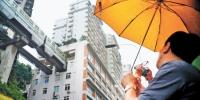 5月24日,尽管重庆下着小雨,游人还是来到网红景点李子坝轻轨站拍照。 记者 卢越 摄 - 重庆新闻网