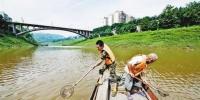 7月15日,巴南区木洞镇五布河入江口段,大雨过后,河面漂浮物增多,两名工人正在船头清漂。首席记者 谢智强 摄 - 重庆新闻网